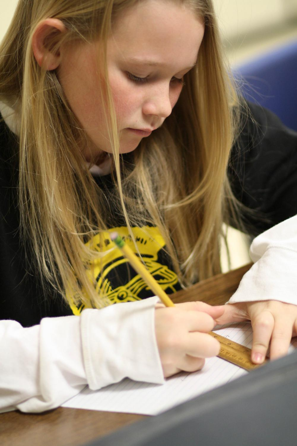 Mackenzie Trout finds areas of triangles. Photo by Yearbook student, Katie Deplanche.