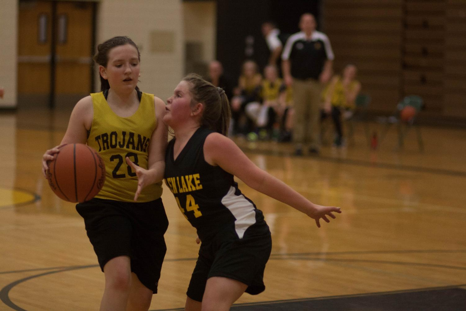 Sydney Rademacher protects the ball from Glen Lake player. Photo by Yearbook student, Lexi Minzey.