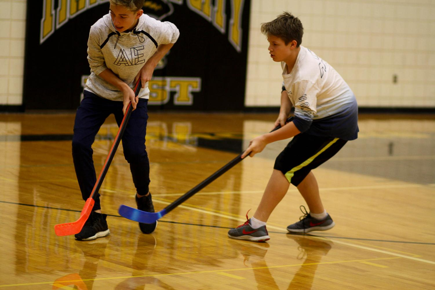 Joe Hebert and Matt Cook race for the puck in floor hockey. Photo by Yearbook student, Ashley Piper.
