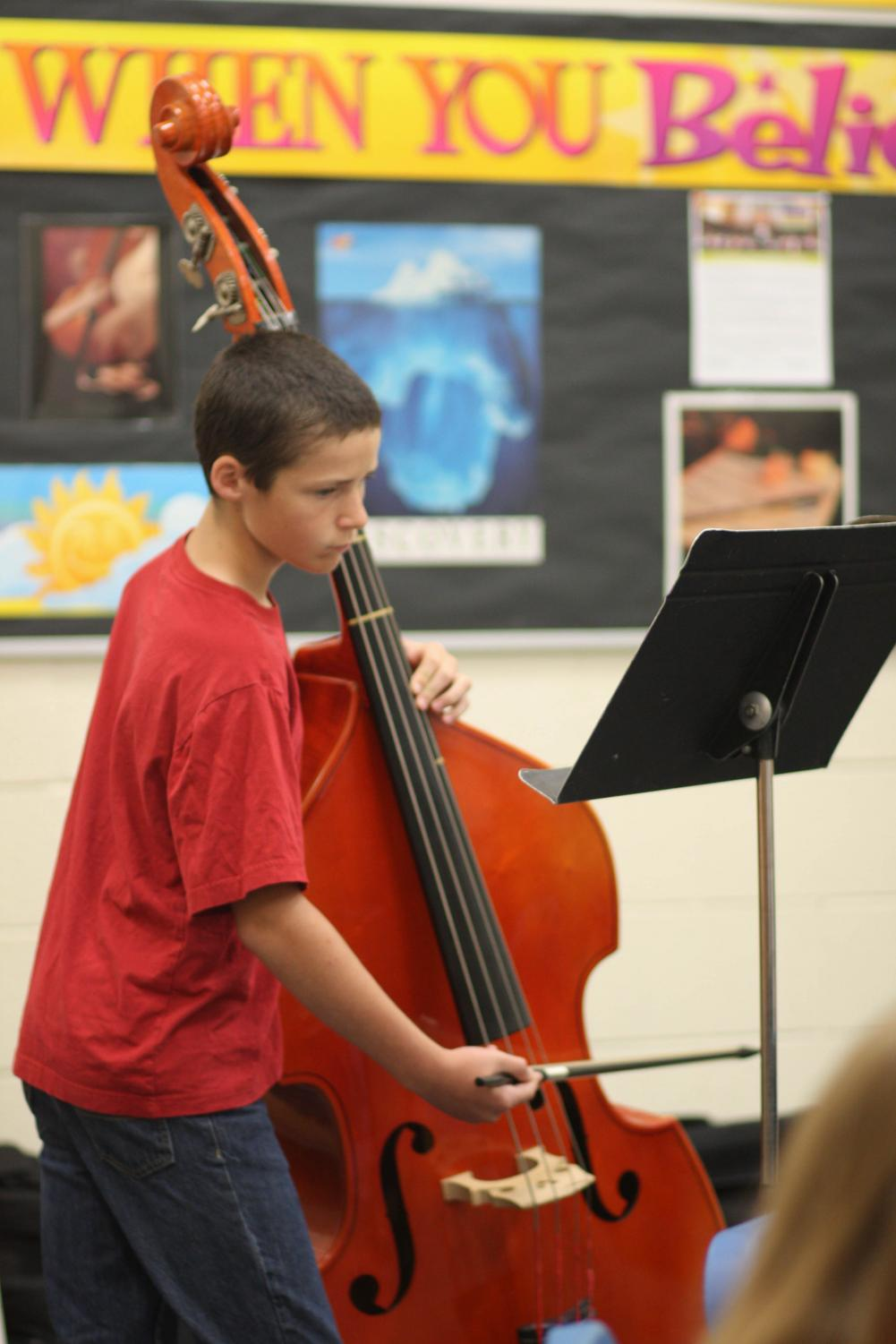 A student plays cello in orchestra.