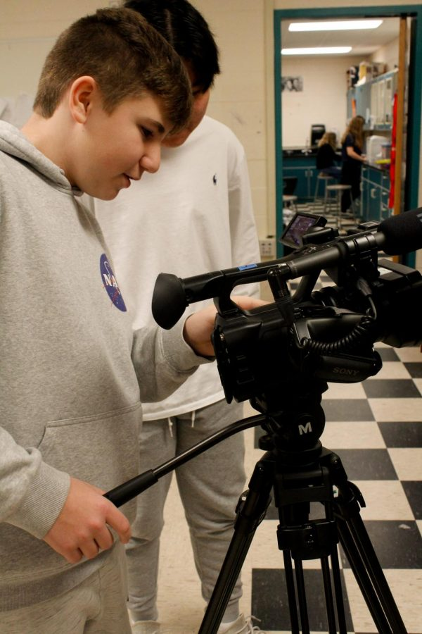 Ryan Grubbs(24) is filming students in DMC class with a video camera.