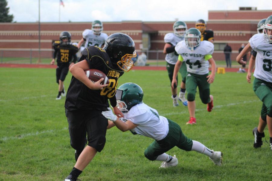 EMS football player dodges a West player.